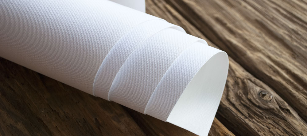 What is rolled canvas print. Brilliant white canvas roll on wooden surface.