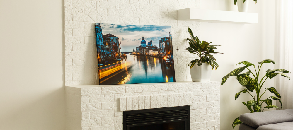 How much does it cost to make a canvas print. Photo canvas print on mantel with plant nearby.