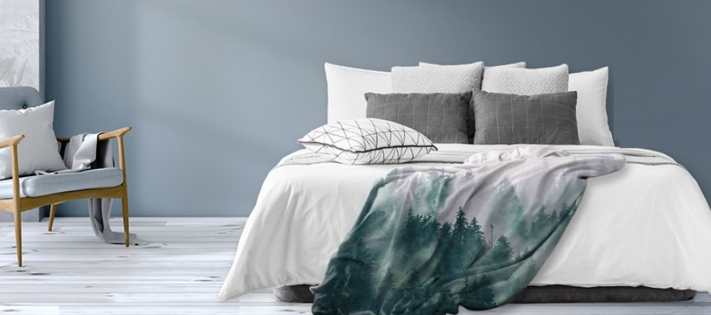 Where to create a blanket with your own picture on it. Personalized blanket with forest photo on bed.