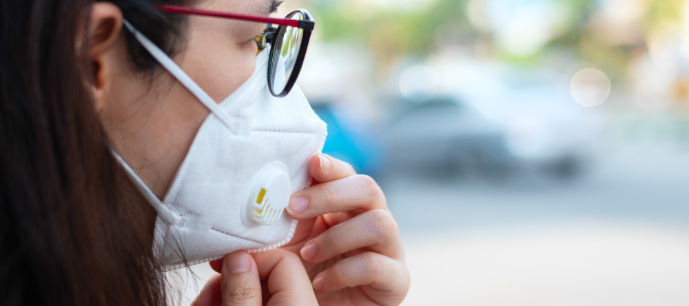What is a medical face mask. Profile of young woman wearing respirator and glasses.