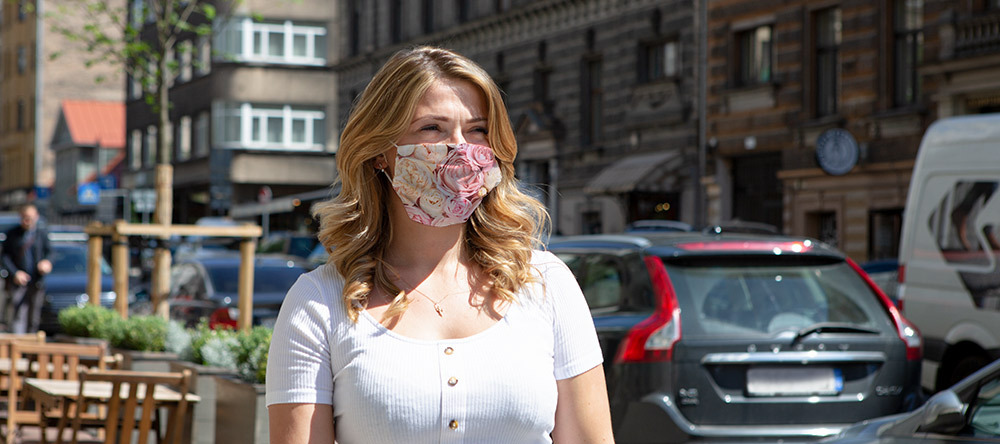 When you should wear a face mask. Young woman with face mask walking on street.