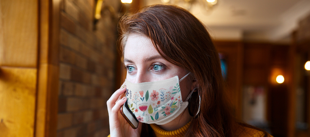 When you should wear a face mask. Young woman wearing face mask and speaking on her phone.