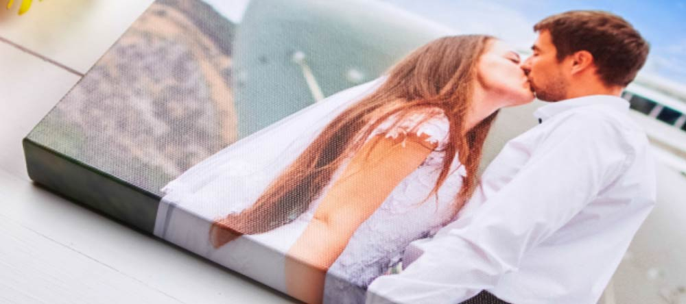 The Pros & Cons of Canvas Printing. Wedding photo canvas print with couple kissing.