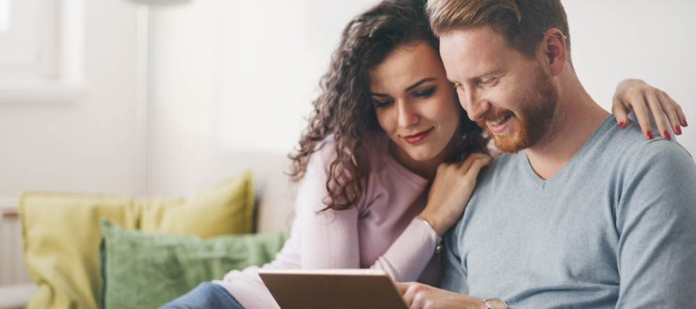 Custom-Made Canvases: 10 Myths Debunked. Young couple looking for canvas prints online on tablet.