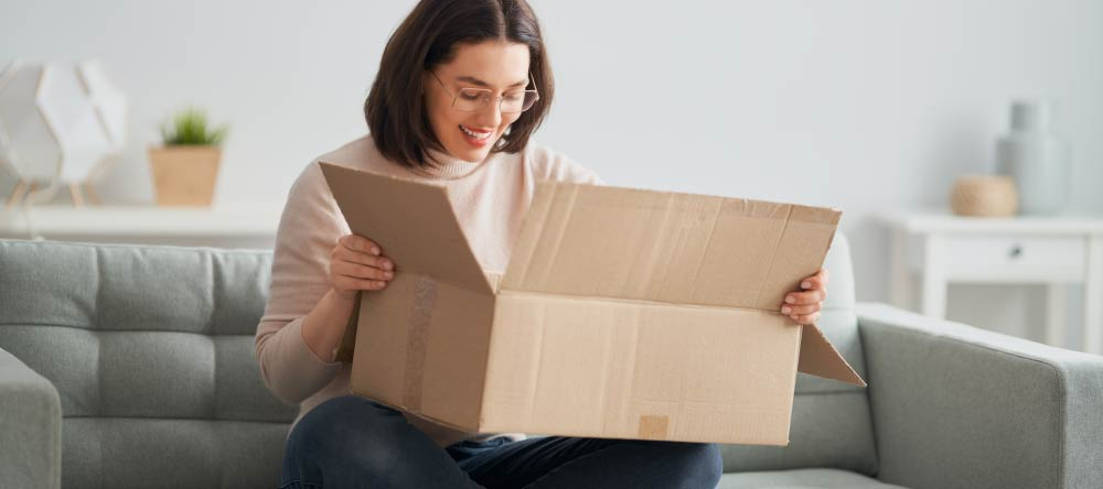 What is the Best Place to Get Canvas Prints on a Budget? Young woman opening her just delivered order.