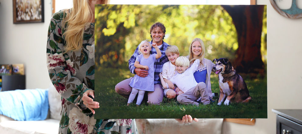 What is a canvas print. Woman holding family photo canvas print.