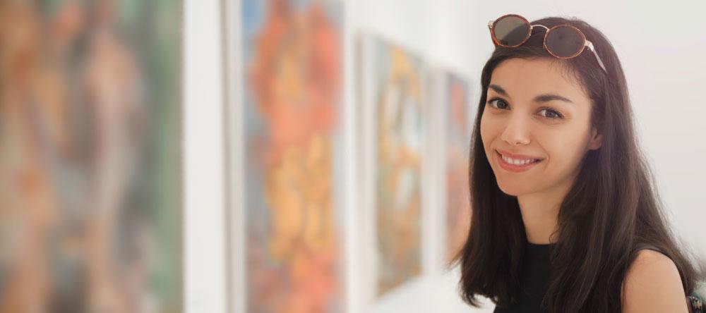 Wieso sollte ich eine Leinwand online bestellen? Besucherin im Musuem schaut sich eine Kunstausstellung an.