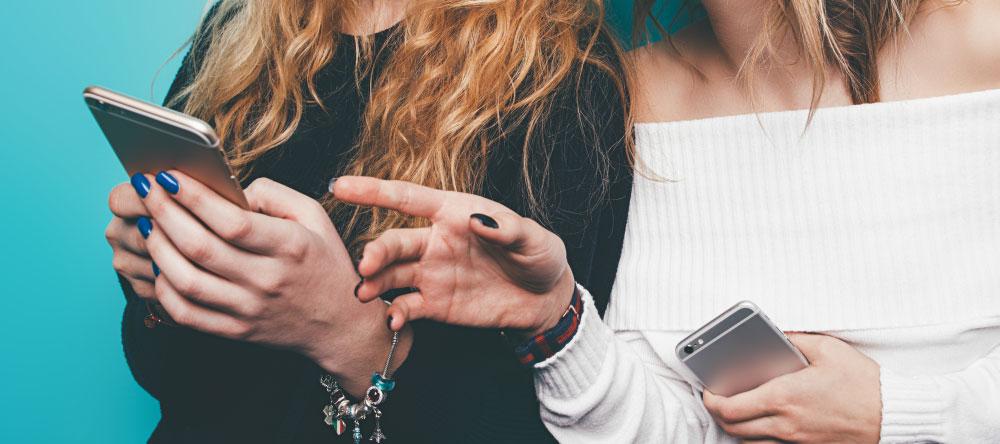 Wieso sollte ich eine Leinwand online bestellen? Zwei Frauen benutzen ihre Mobiltelefone.