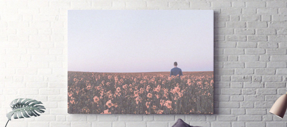 Was ist der Unterschied zwischen einem Poster und einer Leinwand. Leinwand an einer weißen Backsteinwand.