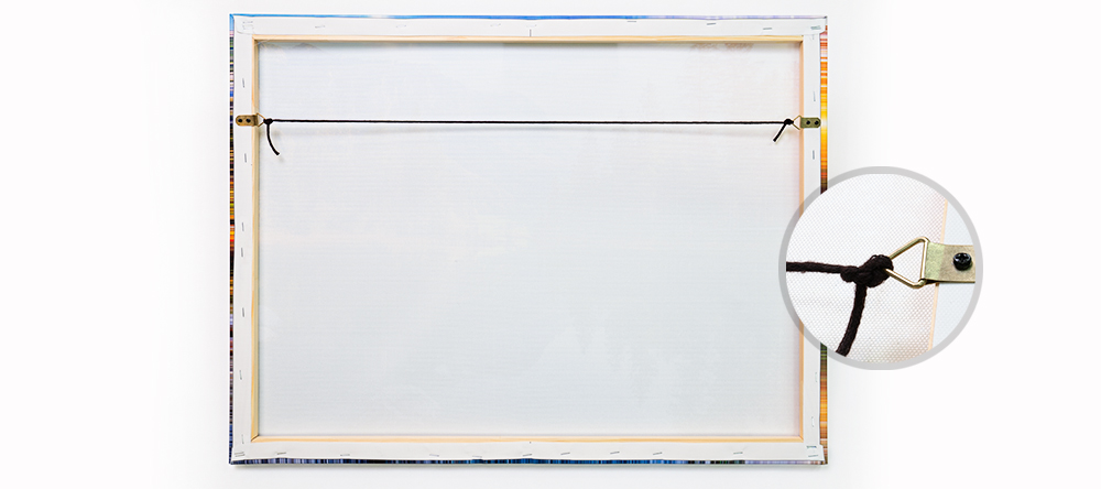 How to hang your canvas print. The complete guide. Cord through the triangular D-rings.