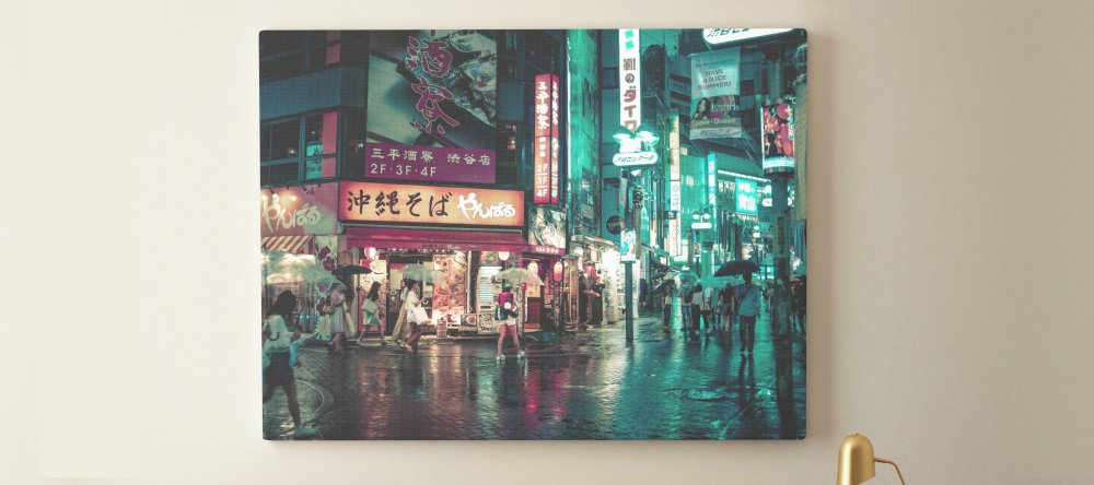 What is lamination on canvas prints. Print on wall showing urban nighttime scene.