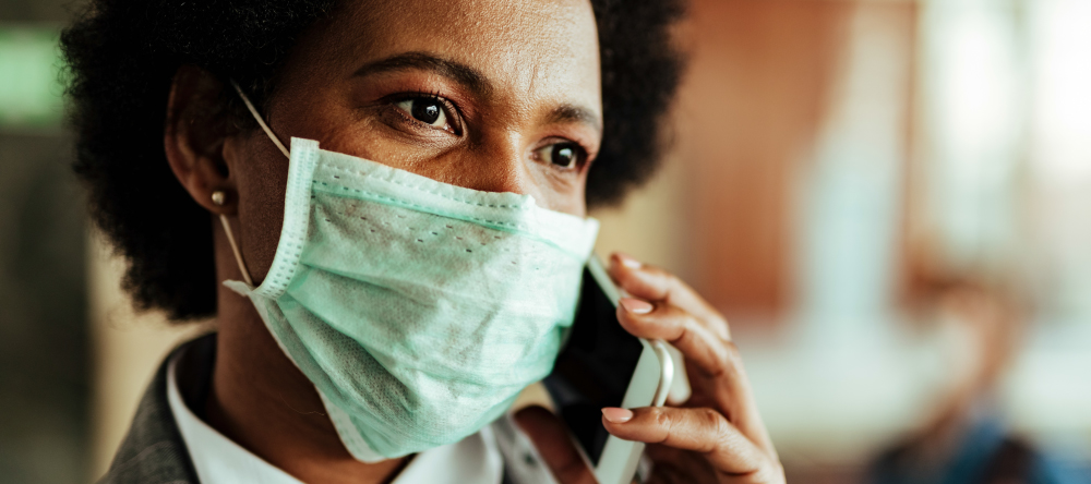 Personalised face masks. African American business woman wearing medical face mask and talking on phone.