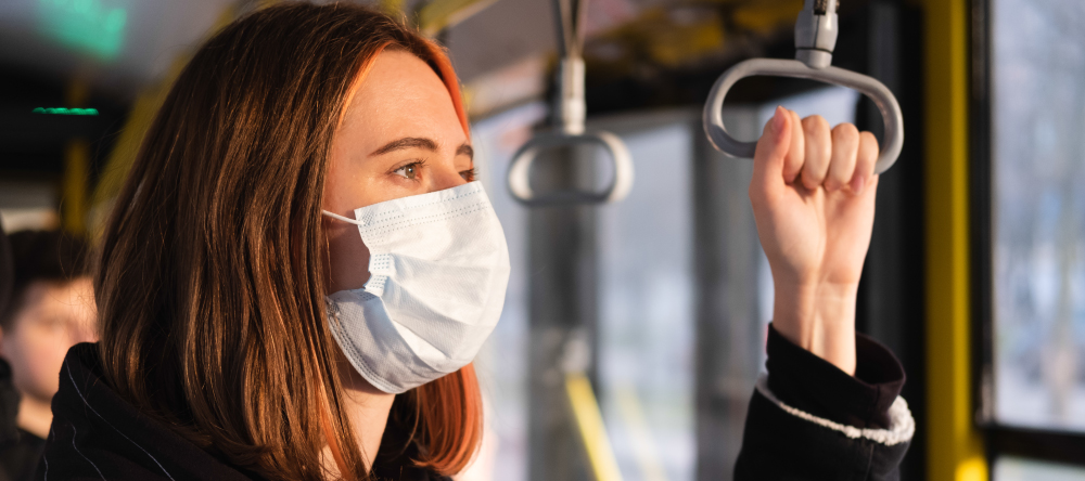 Personalised face masks. Young woman wearing medical face mask in public transport.