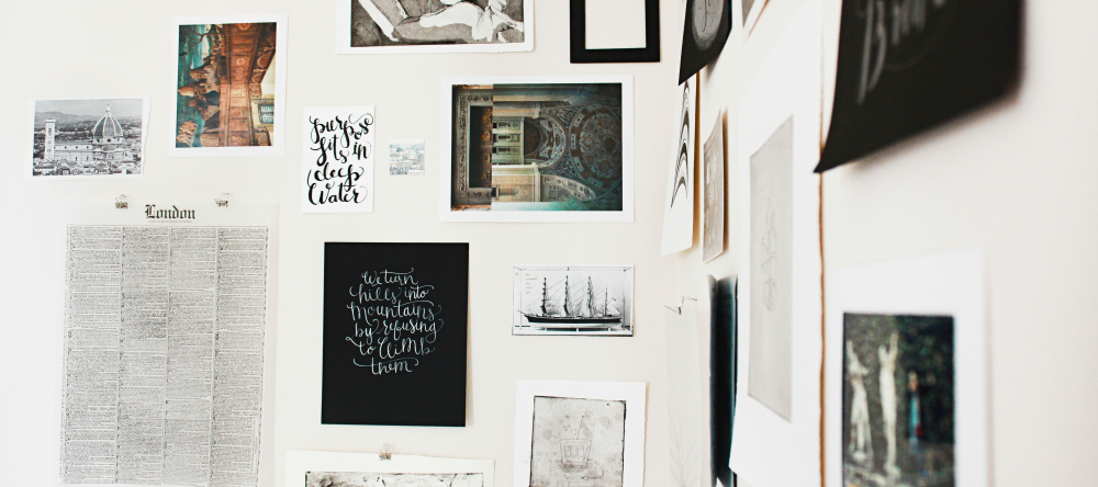 The Difference Between Canvas and Poster Prints: Which Should You Choose? Wall covered with posters of different sizes.