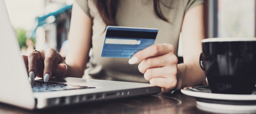 How Much Does a Canvas Print Cost? Woman holding her credit card for online shopping.