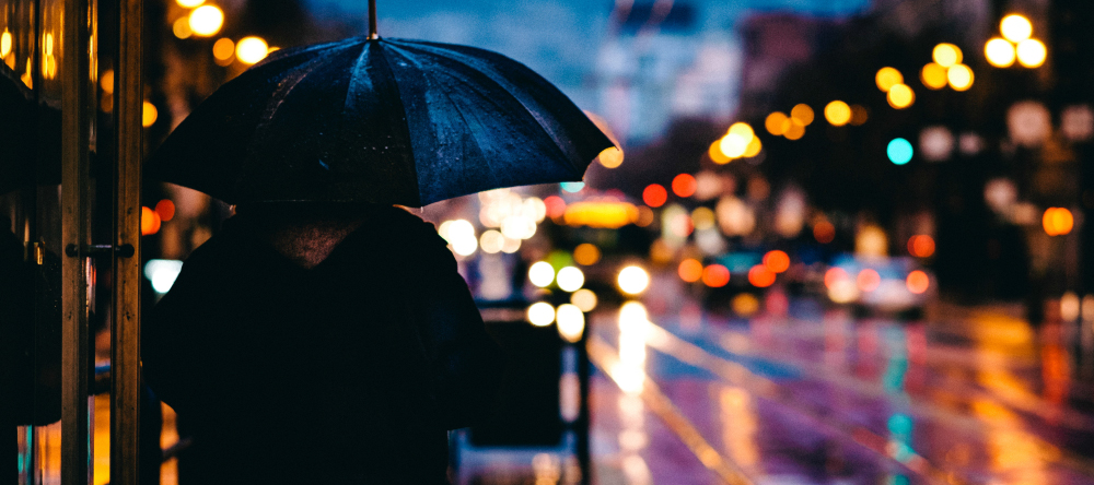 New photo trends for 2021. Man with an umbrella on a rainy evening.