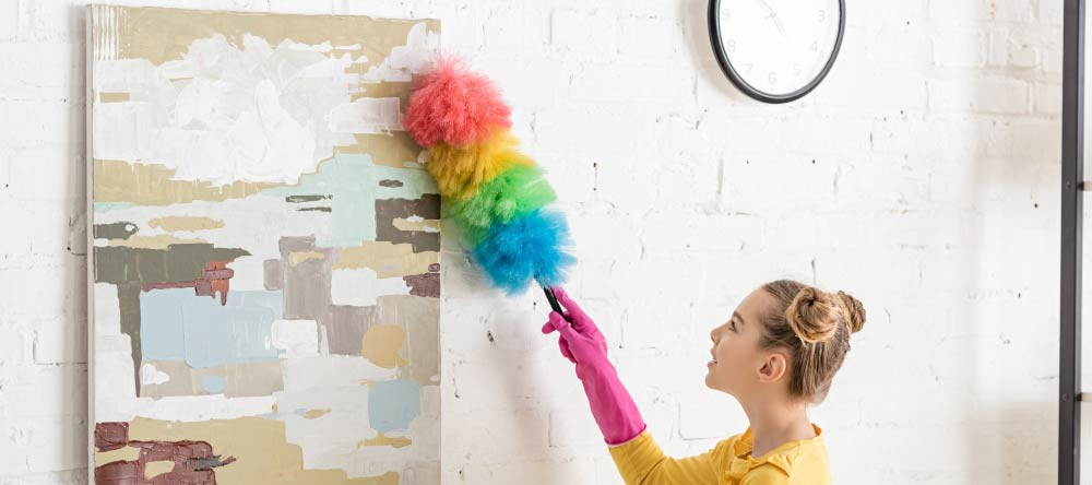 How to Clean a Canvas Print. Young lady clearing dust off her canvas.