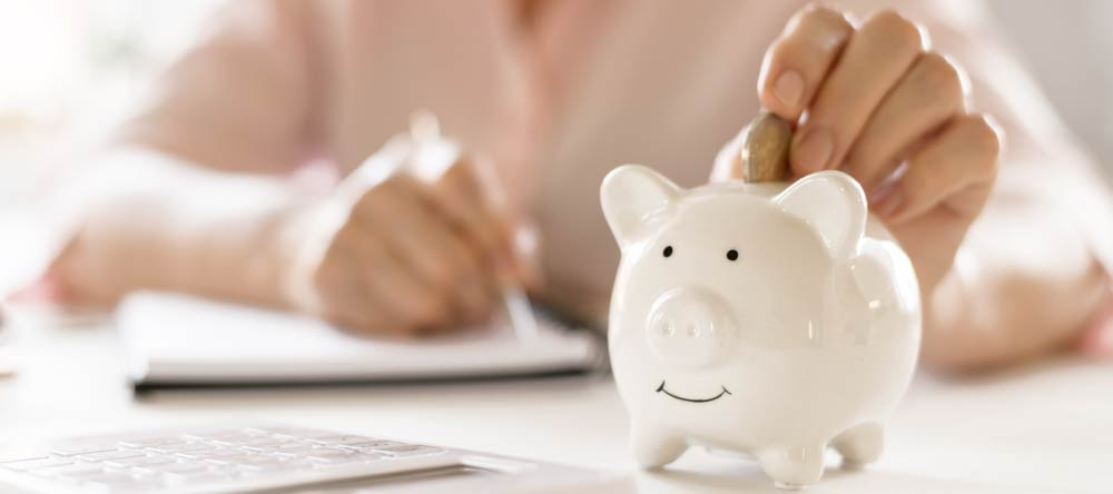 Where to Print Pictures Near Me. Woman calculating her budget with piggy bank next to her.